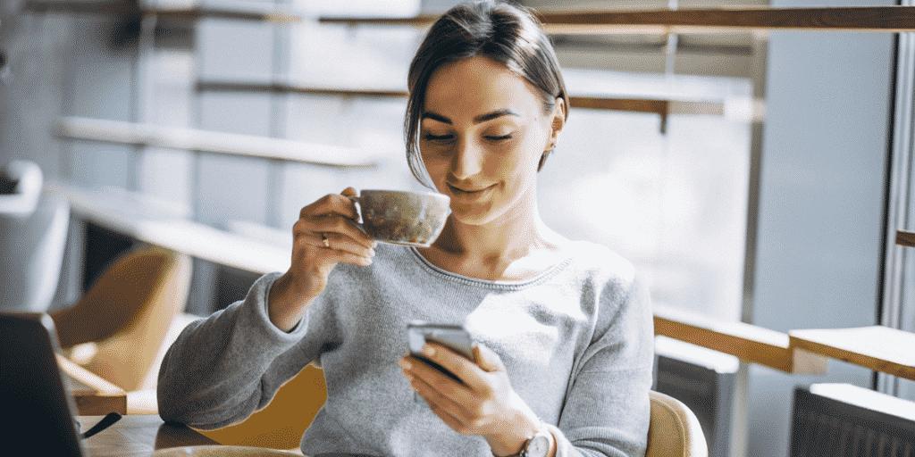 mulher olhando celular marketing de conteúdo E-clínica marketing digital