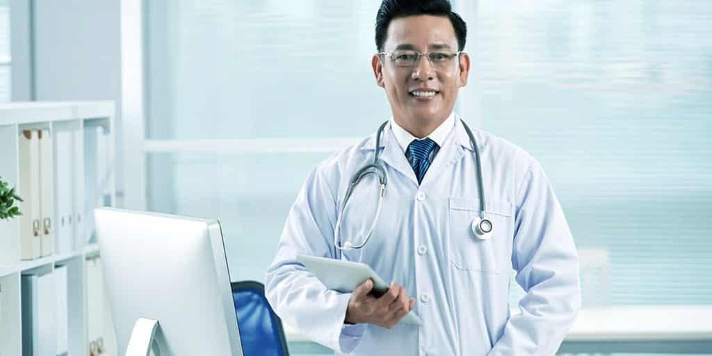 médico em consultório sorrindo segurando um tablet e conferindo o marketing digital para clínicas através do facebook ads