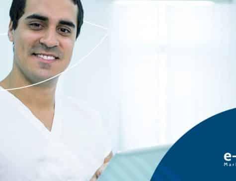 dentista sorrindo segurando tablet pesquisando sobre marketing digital para dentistas