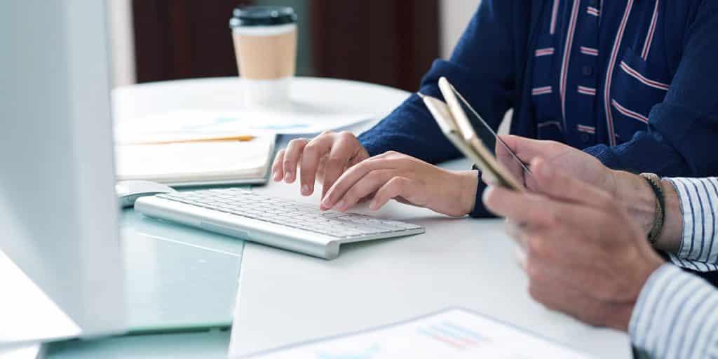 mãos de mulher usando computador e mãos de homem usando tablet trabalhando no marketing digital para médicos com palavras-chave