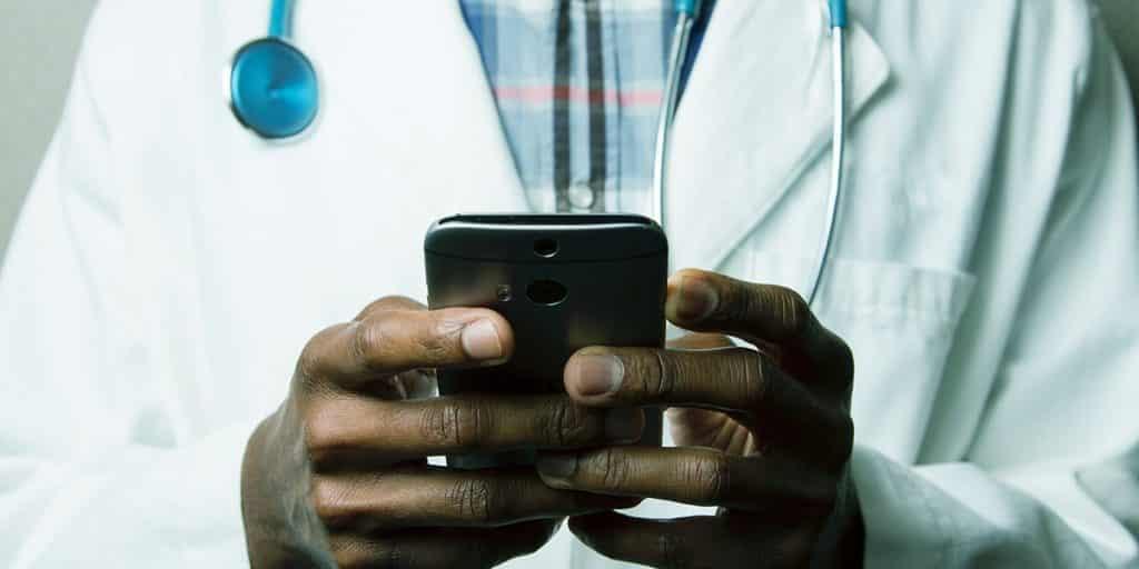 médico ao celular fazendo SEO médico