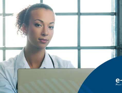 Médica em frente a um laptop gerenciando suas redes sociais no marketing digital para médicos
