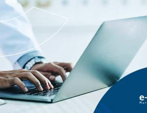 mãos de médica ao laptop escrevendo em blog no seu marketing para clínicas