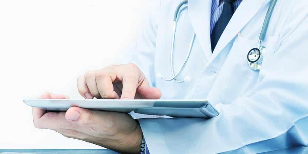 mãos de médico usando tablet que visita site de marketing para médicos