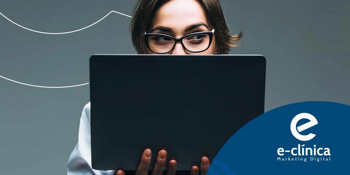 médica sorrindo por trás de laptop visita site sobre marketing para médicos